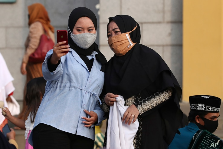 Muslim women wearing face masks as precaution against the new coronavirus outbreak, take a selfie after an Eid al-Adha prayer…