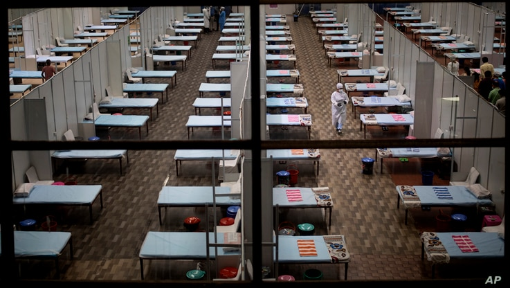 A hospital staff walks past rows of beds at a makeshift COVID-19 care center at an indoor sports stadium in New Delhi, India,…