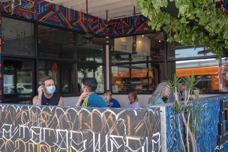 Patrons observing social distancing rules sit outdoors at the Guerrilla Tacos restaurant in Los Angeles, Friday, July 3, 2020…
