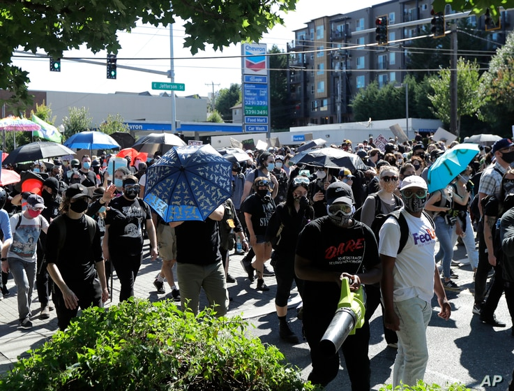 Protesters march near the King County Juvenile Detention Center, Saturday, July 25, 2020, in Seattle in support of Black Lives…