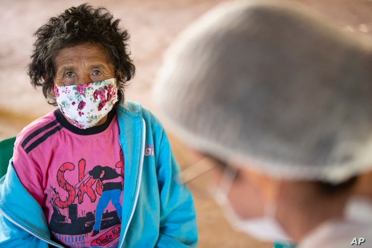 A Guarani Mimbya Indigenous woman waits to be tested for COVID-19 by health workers from the Butantan Institute in Cananeia,…