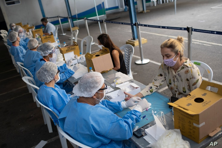Health workers take residents' blood samples at a testing site for COVID-19 amid the new coronavirus pandemic in Rio de Janeiro…