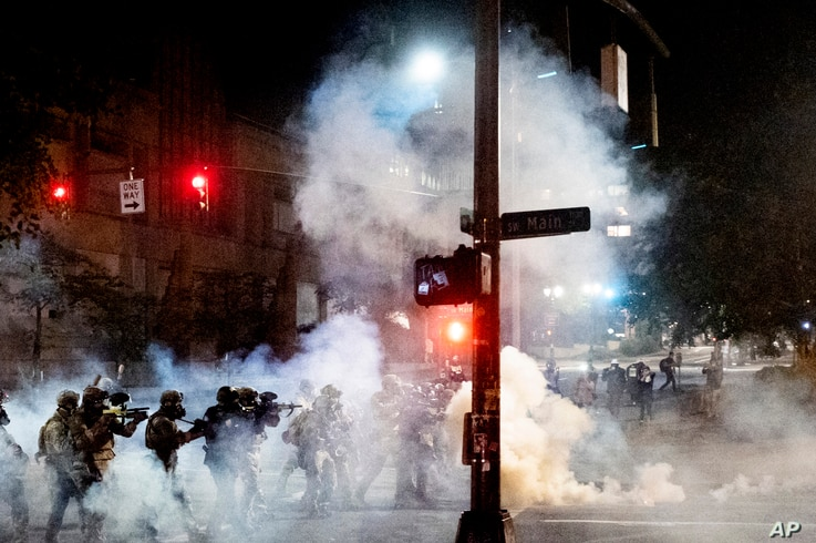 Federal agents use crowd control munitions to disperse Black Lives Matter protesters near the Mark O. Hatfield United States…