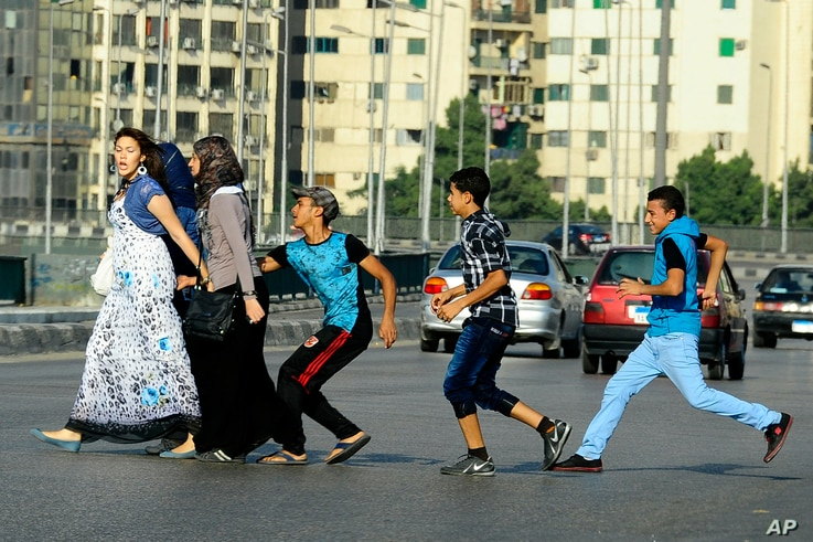 FILE - In this Aug. 20, 2012 file photo, an Egyptian youth, trailed by his friends, gropes a woman crossing the street with her…