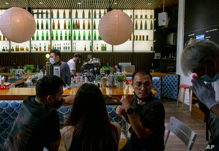 A steward greets a group of customers at a pub in Bangkok, Thailand, Wednesday, July 1, 2020. Thailand has begun a fifth phase…