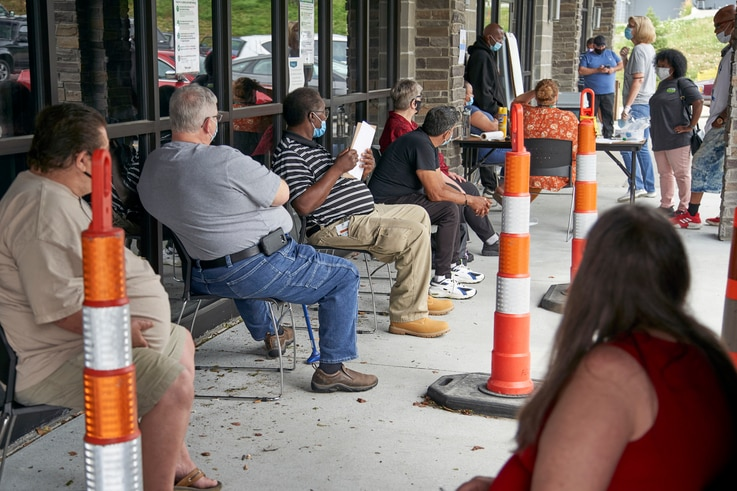Job seekers exercise social distancing as they wait to be called into the Heartland Workforce Solutions office in Omaha, Neb.,…