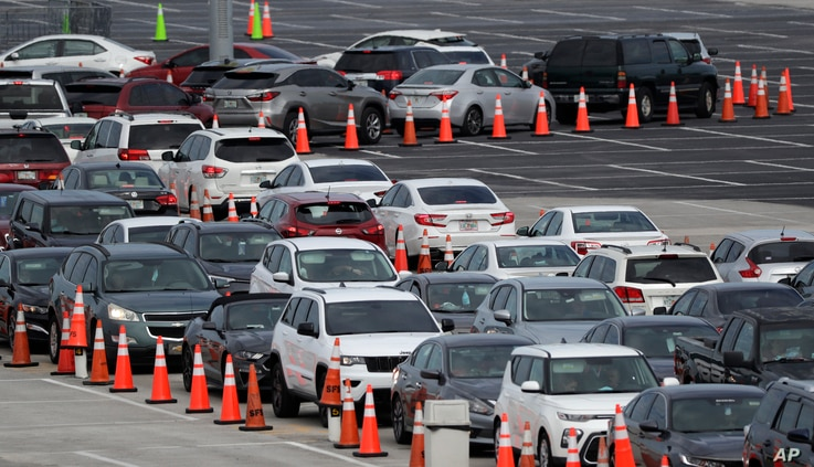 Lines of cars wait at a drive-through coronavirus testing site, Sunday, July 5, 2020, outside Hard Rock Stadium in Miami…