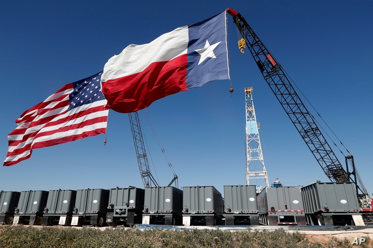 An American and Texas flag fly from the tops of cranes near an oil rig by the site where President Donald Trump delivered…