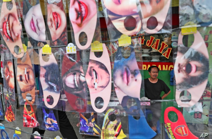 A man is seen through a display of fun face masks for sale at a roadside stall in Jakarta,Indonesia, Thursday, July 16, 2020…