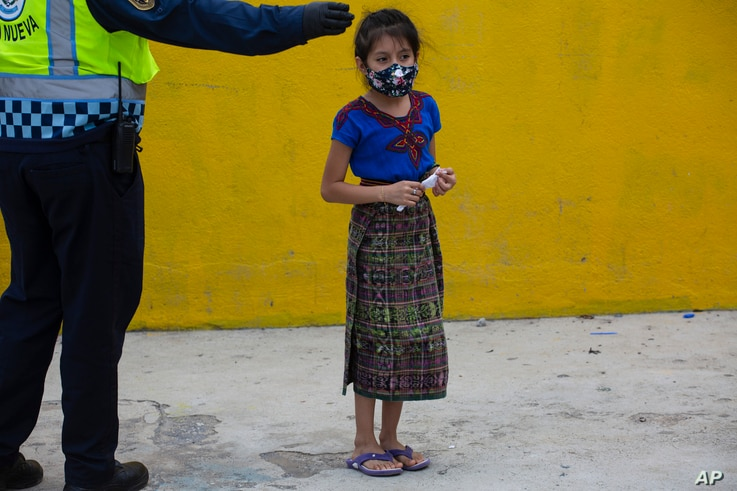 A child wearing a protective face mask, stands in line to receive a free meal in the Peronia neighborhood of Villa Nueva,…