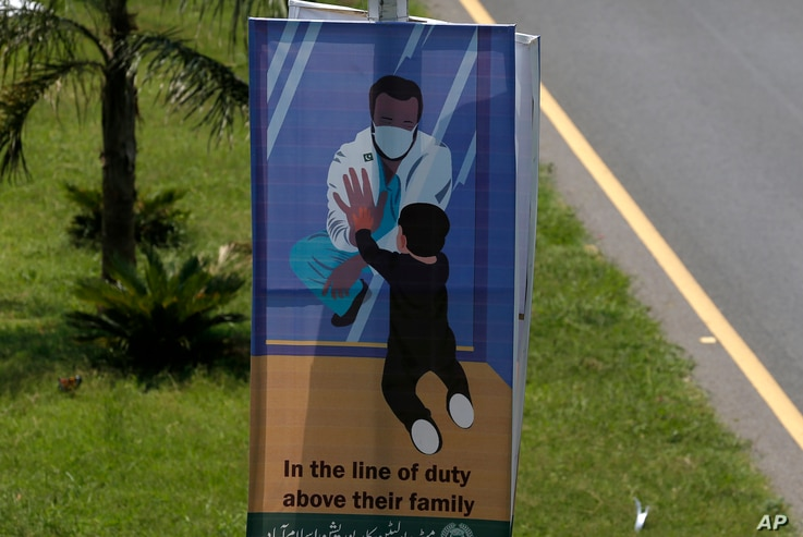 A banner paying tribute to doctors who are offering care and saving lives during the coronavirus pandemic is displayed on a…