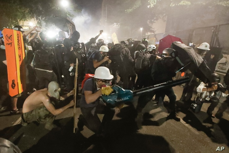 Demonstrators huddle and blow back tear gas with leaf blowers during clashes with federal officers during a Black Lives Matter…