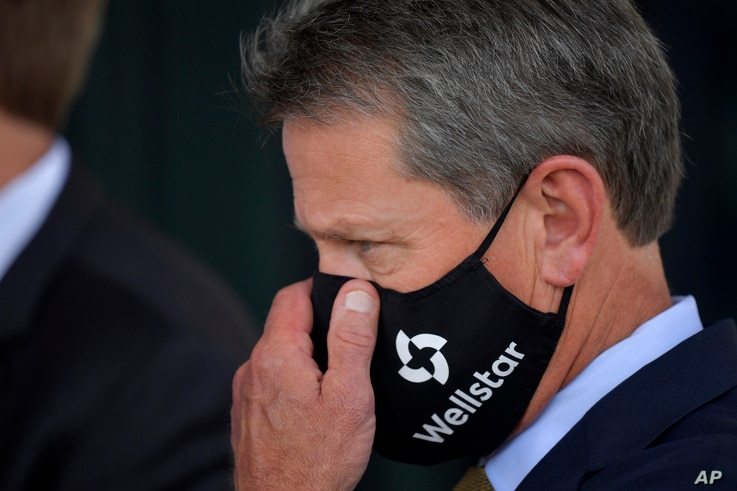 Georgia Gov. Brian Kemp adjusts his mask prior to a bill signing at Wellstar Kennestone Hospital where the hospital opened a…