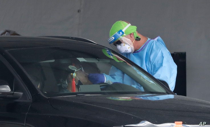 A healthcare worker takes a swab sample from a driver at a drive-through COVID-19 testing site outside Hard Rock Stadium,…