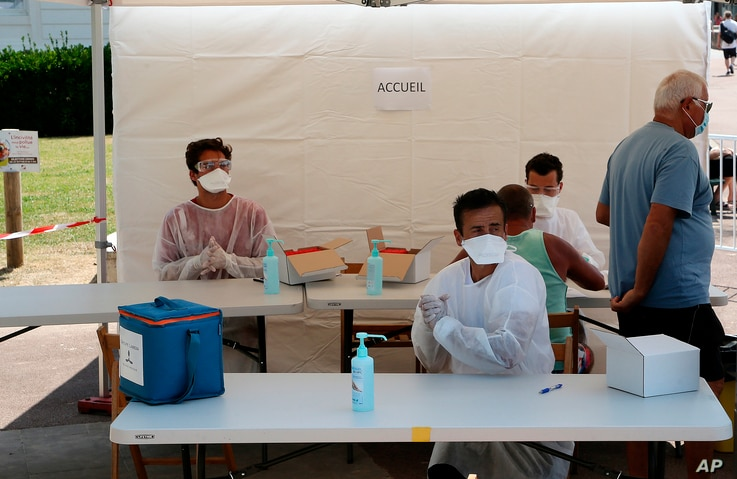 Health-care workers prepare to test people with COVID-19 symptoms near the beach in Saint Jean de Luz, southwestern France,…