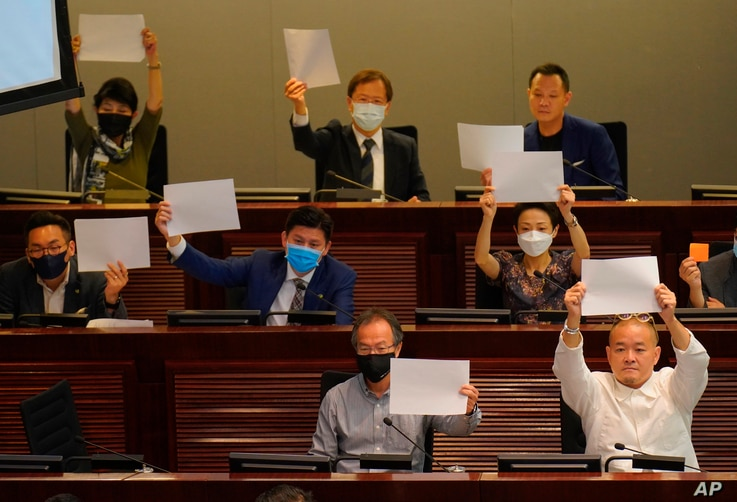 Pro-democracy lawmakers raise white papers to protest during a meeting to discuss the new national security law at the…