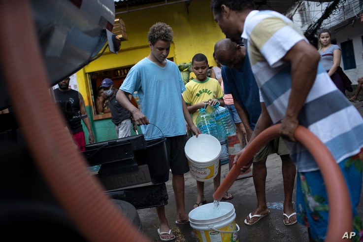 Residents fill their buckets with water provided by the local water utility from a tanker truck, amid the new coronavirus…