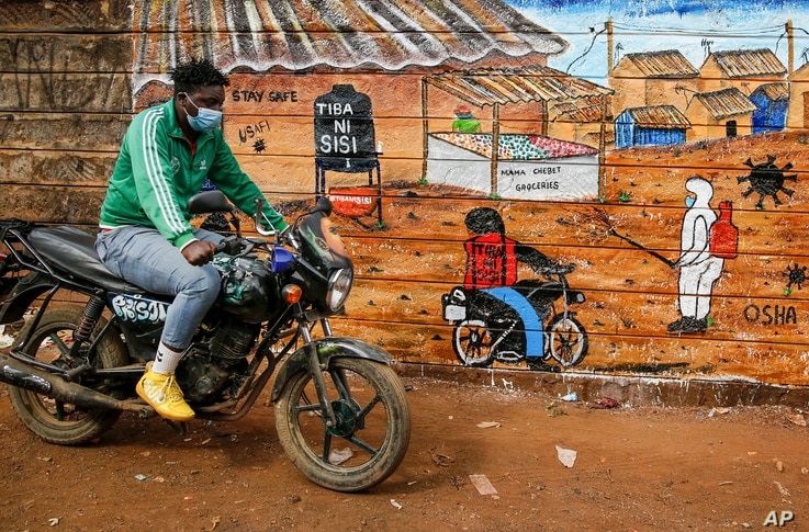 A man rides a motorcycle past an informational mural warning people about the dangers of the new coronavirus and how to prevent…