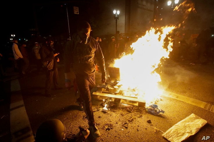 A protester walks past a bonfire set at an intersection during a Black Lives Matter protest at the Mark O. Hatfield United…