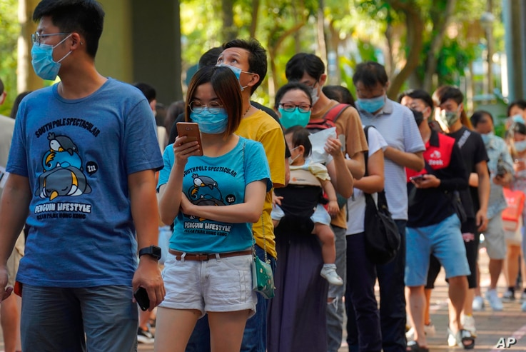 People queue up to vote in Hong Kong Sunday, July 12, 2020, in an unofficial primary for pro-democracy candidates ahead of…