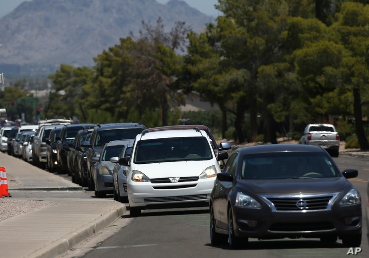 Motorist wait in lines to get tested at a drive-thru coronavirus testing site at South Mountain Community College, Thursday,…