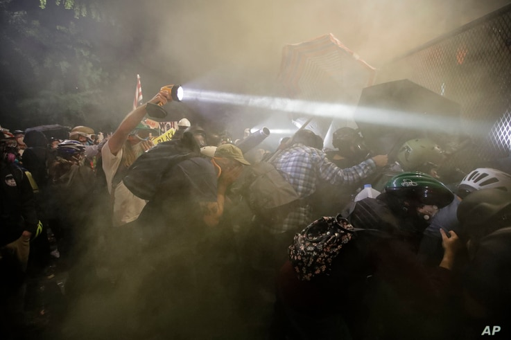 Demonstrators push on a fence as tear gas is deployed during a Black Lives Matter protest at the Mark O. Hatfield United States…