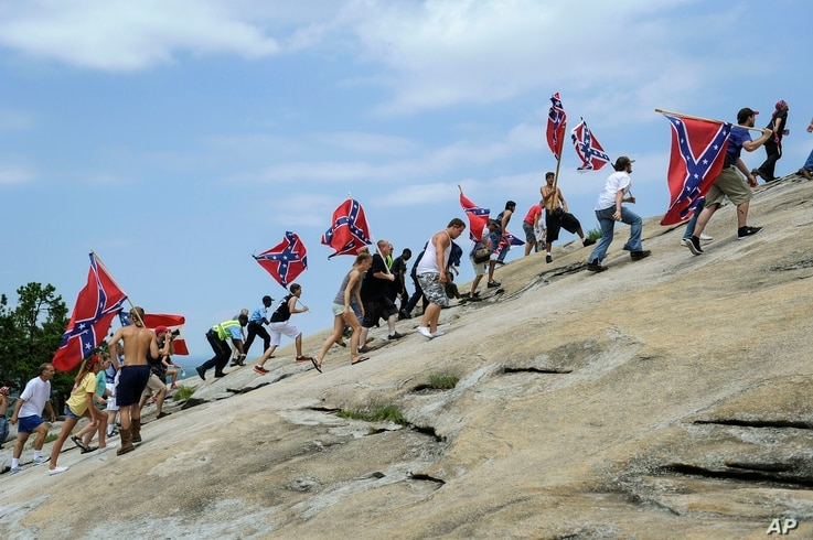 FILE - In this Aug. 1, 2015 file photo, Confederate flag supporters climb Stone Mountain to protest of what they believe is an…