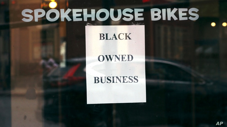 In this Wednesday, June 24, 2020, photograph, a sign in the window informs passersby that Spokehouse Bikes in the Upham's…