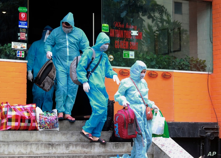 People walk toward an ambulance to be driven to a hospital for quarantine relating to a suspected COVID-19 case in Hanoi,…