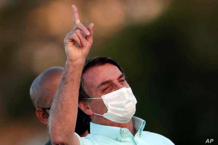 Brazil's President Jair Bolsonaro, who is infected with COVID-19, wears a protective face mask as he attends a Brazilian flag…