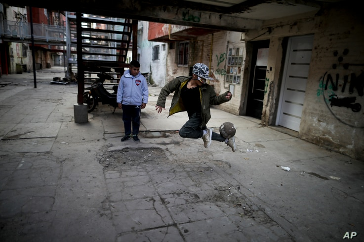 A youth controls a soccer ball outside apartment buildings in the Fuerte Apache neighborhood where soccer star Carlos Tevez…