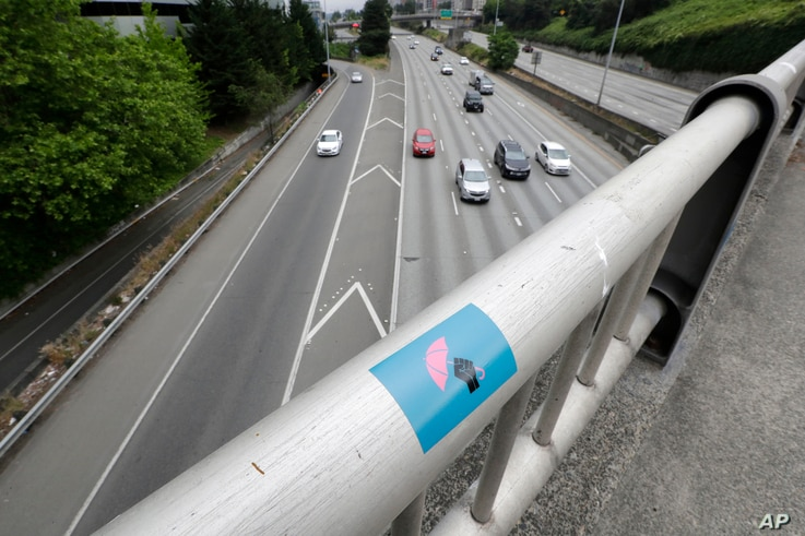 A protest sticker is posted on a handrail above Interstate 5 Saturday, July 4, 2020 in Seattle, where two protesters on the…