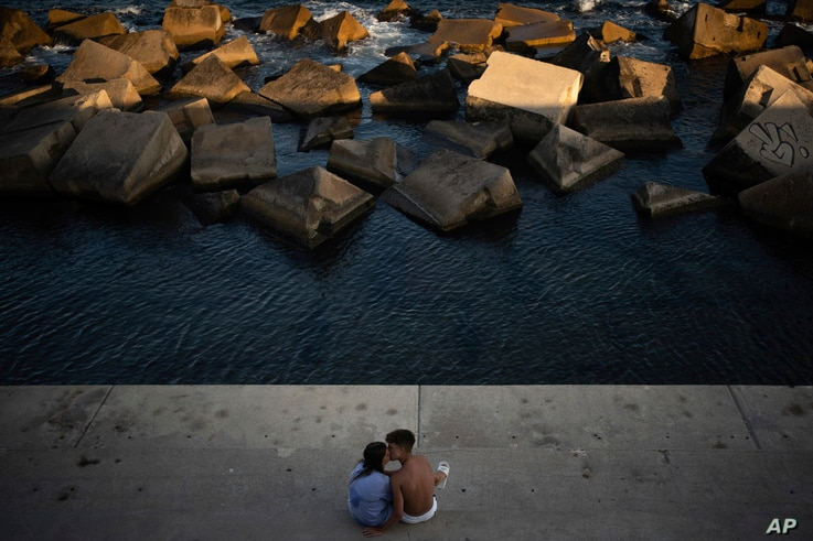 A couple kisses as they sit by the sea in Barcelona, Spain, Saturday, July 25, 2020. Britain is advising people not to travel…