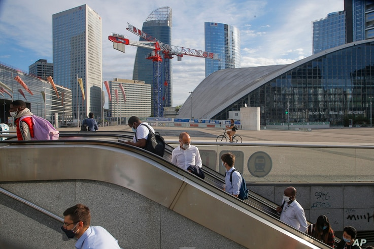 People ride an escalator as they arrive at La Defense business district while wearing a protective face masks as a precaution…