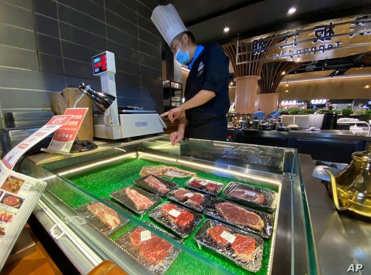 A worker weighs beef products on sale at a food court in Beijing Friday, Aug. 28, 2020. China blocked imports from an…