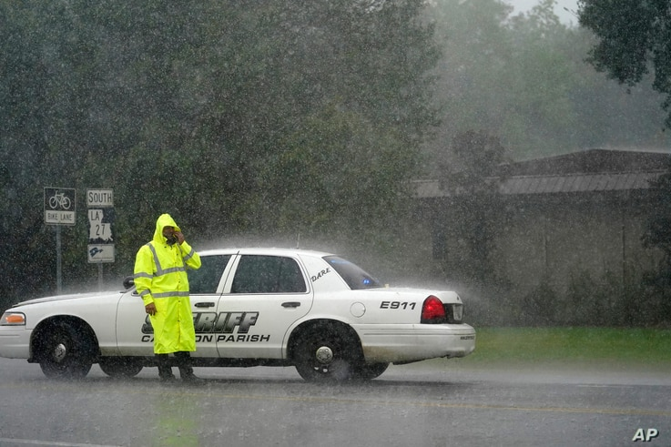 A Cameron Parish Sheriff deputy wipes his face as he mans a roadblock in the rain on LA 27 while residents evacuate Cameron in…