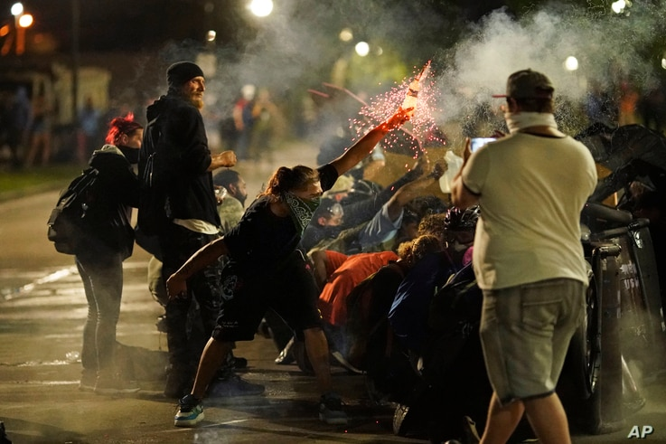 A protester tosses an object toward police during clashes outside the Kenosha County Courthouse late Tuesday, Aug. 25, 2020, in…
