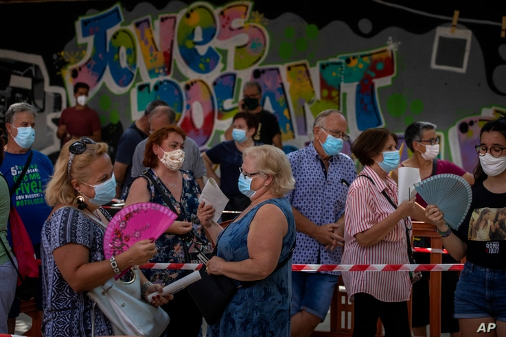 People wearing face masks wait their turn to be called for a PCR test for the COVID-19 at Vilafranca del Penedes in the…