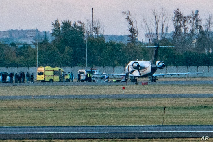 Russian opposition leader Alexei Navalny, center on stretcher, is transported to a German special medical plane at an airport…