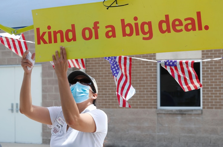 Census worker Marisela Gonzales adjusts a sign at a U.S. Census walk-up counting sight set up for Hunt County in Greenville,…