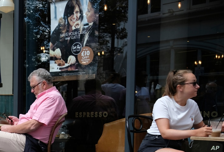 Customers eat at restaurant in central London, Monday, Aug. 3, 2020, next to signs indicating a discount off food. Restaurant…