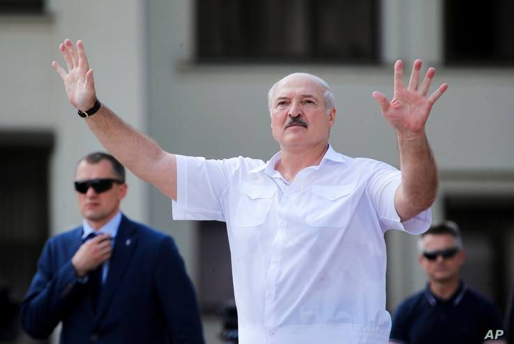 Belarusian President Alexander Lukashenko gestures as he greets his supporters gathered at Independent Square of Minsk, Belarus…