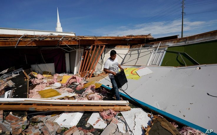 Benjamin Luna helps recover items from the children's wing of the First Pentecostal Church that was destroyed by Hurricane…