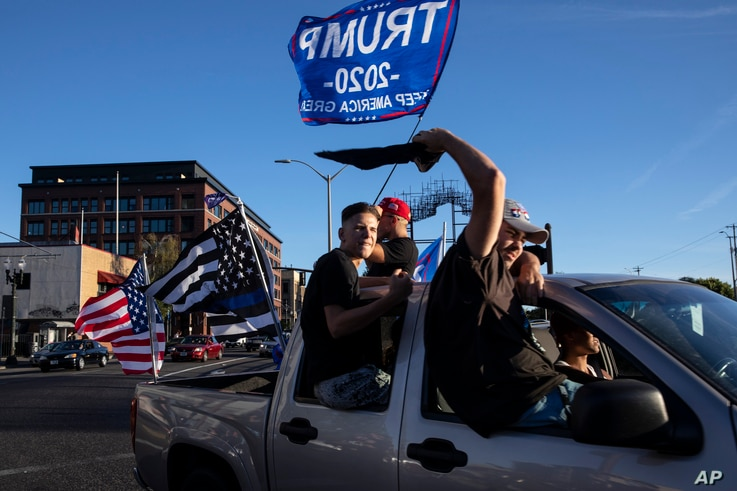 Supporters of President Donald Trump attend a rally and car parade Saturday, Aug. 29, 2020, in Clackamas, Ore., on the way to…