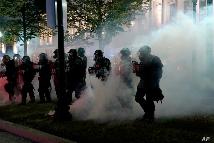 Police clear a park during clashes with protesters outside the Kenosha County Courthouse late Tuesday, Aug. 25, 2020, in…