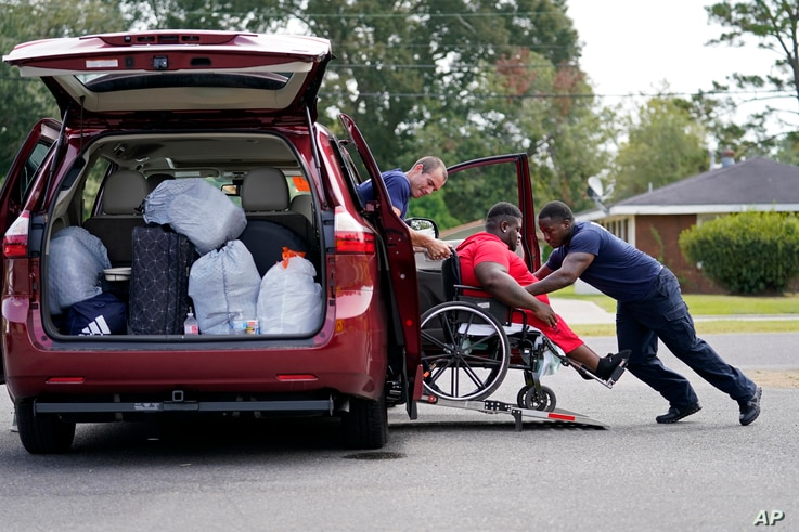 Lake Charles Fire Department personnel Alvin Taylor, right, and Jeremy Harris, left, assist Tim Williams into a transport van…