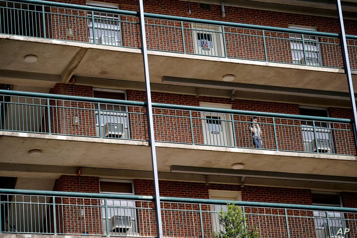 A students stands on the balcony of Ehringhaus dormitory on campus at the University of North Carolina in Chapel Hill, N.C.,…