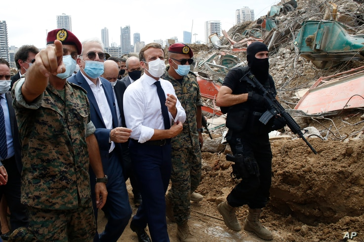 French President Emmanuel Macron, center, visits the devastated site of the explosion at the port of Beirut, Lebanon, Thursday...