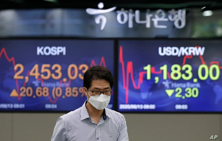 A currency trader walks near screens showing the Korea Composite Stock Price Index (KOSPI), left, and the foreign exchange rate…