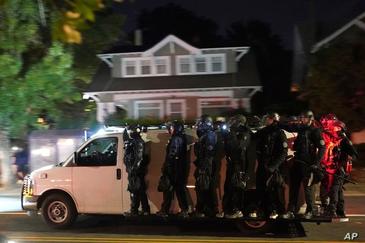 Portland police hang off the side of a riot van while searching for protesters in the Laurelhurst neighborhood after dispersing…